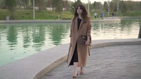 Spokojna młoda brunetka w sukni i żakiecie chodzi blisko stawu w jesień parku zdjęcie wideo
