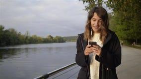 Spokojna młoda kobieta słucha muzyka i odprowadzenie blisko rzeki zbiory wideo