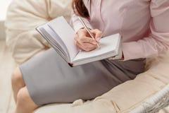 Spokojna młoda kobieta wpisuje w notatniku obraz stock