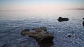 Spokojna ocean fala brzeg idylliczna plaża z turkus wody niebieskiego nieba chmur skały białymi otoczakami i kamieniem zbiory