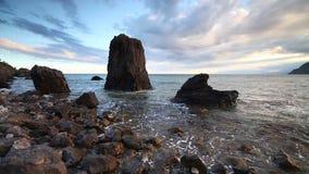 Spokojna ocean fala brzeg idylliczna plaża z turkus wody niebieskiego nieba chmur skały otoczakami i kamieniem zbiory