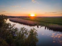 Spokojna powierzchnia rzeka, pomarańczowy zmierzch, zieleni pola i łąki w zaciszności, grżemy lato wieczór fotografia royalty free