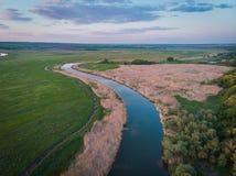 Spokojna rzeka płynie wzdłuż równiny Brzeg rzeki, przerastający z płochami, zielone łąki Piękna sceneria od ptasiego ` s oka wido zdjęcia stock