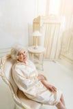 Spokojna stara kobieta relaksuje na karle obrazy royalty free