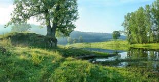 Spokojna stojąca woda rzeka na tle lasowy skłon Obraz Stock
