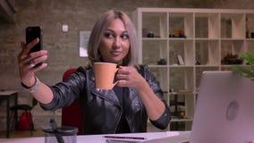 Spokojna szczęśliwa caucasian blondynki kobieta próbuje brać obrazki z jej filiżanką podczas gdy siedzący w jaskrawy ceglany biur