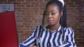 Spokojna unjoyful afrykańska kobieta patrzeje cred komputer z consentration w th ceglanym studiu podczas gdy siedzący przy jej dz