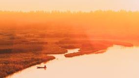 Spokojna woda jezioro, rzeka i wioślarska łódź rybacka przy pięknym wschodem słońca w jesień ranku, Rybak jest w łodzi fotografia stock