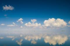 Spokojna woda z chmurami Zdjęcia Stock