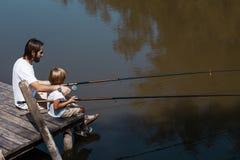 Spokojni mężczyźni światowi Ojciec i mały syn, oba w białych t koszula, siedzimy na drewnianym moście łowić i obraz stock