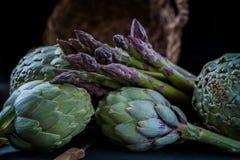 Spokojny życie karczochy i asparagus na nieociosanym koszu na tła zakończenia bocznego widoku depresji kluczu Fotografia Royalty Free