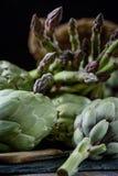 Spokojny życie karczochy i asparagus na nieociosanym textured tło bocznego widoku depresji kluczu Obrazy Stock