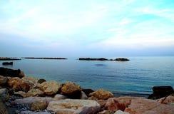 Spokojny Adriatycki morze otaczający masywnymi skałami pod bławym niebem obrazy stock