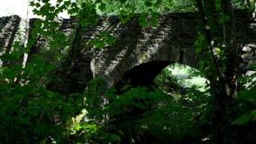 Spokojny bieżący strumyk pod kamiennym stopa mostem w magicznym punkcie z jarzębatymi cieniami od słońca przez drzewnych liści w  zbiory wideo