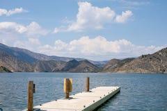 Spokojny spokojny dok przy błękitnym jeziorem otaczającym górami Obrazy Stock