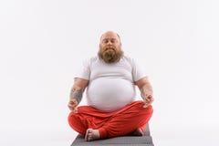 Spokojny gruby facet robi joga fotografia stock
