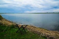 Spokojny jeziorny widok Falcowanie rybaka krzesło przy brzegowym Błękitnym chmurnym dżdżystym niebem obraz stock