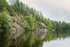 Spokojny jezioro i skalisty brzeg z drzewami obrazy stock