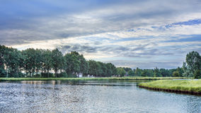 Spokojny krajobraz z kanałem, drzewami i błękitnym aky przy świtem, Fotografia Stock