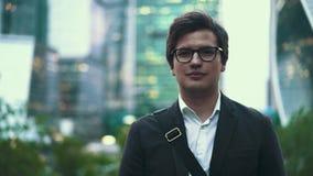 Spokojny młody biznesmen, ono uśmiecha się kamera w dużym mieście, lato zbiory wideo