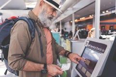 Spokojny nieogolony emeryt pisać na maszynie na terminal Obrazy Stock