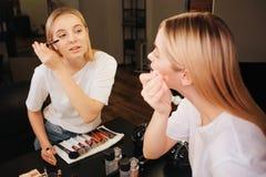 Spokojny pokojowy młodej kobiety spojrzenie w lustrze w piękno pokoju Używa tusz do rzęs Muśnięcia na stole obrazy stock