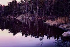 Spokojny zmierzch na jeziorze nawadnia z drewnianym odbiciem na spokoju Zdjęcia Stock