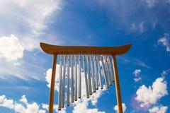 Spola musikaliska chimes på bakgrunden av blå himmel arkivfoton