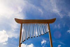 Spola musikaliska chimes på bakgrunden av blå sommarhimmel royaltyfria foton