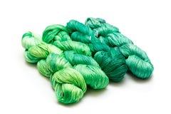 Spolar av den gröna tråden på vit bakgrund royaltyfri foto