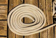 Spole av det vita repet på den Wood pir Fotografering för Bildbyråer