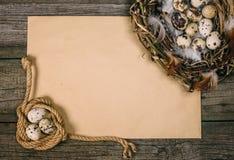 Spole för bästa sikt av repet med vaktelägg i en sida och redet i andra sidan av arket av papper för text på lantligt trä royaltyfri bild