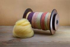 Spole för snurrhjul som fylls med hand rotert garn som göras av sheep'sull med en hög av gult ströva för merino Royaltyfria Bilder