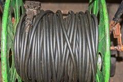 Spolen med elektrisk ett spolat tillbaka kabel- och hålighetsvartband arkivfoto