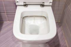 Spolning i toaletten Den rena vita toaletten spolar vatten, closeupfoto fotografering för bildbyråer