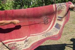 Spolverando una coperta - il metodo tradizionale di pulizia del tappeto Immagini Stock Libere da Diritti