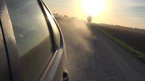 Spolveri l'aumento dall'automobile delle ruote dell'automobile che guida sul sole rurale di sera della strada della ghiaia in cie archivi video