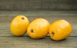 Spondiaspurpurea - läcker tropisk frukt - träbakgrund royaltyfri foto