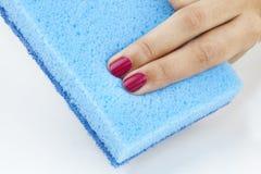 Sponge. Women finger pressing blue sponge Royalty Free Stock Photos