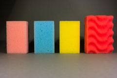 Sponge army. Stack of colorful sponges in a row Royalty Free Stock Images