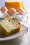 Sponge Cake. On plate with eggs and ingredients and whisk in background Royalty Free Stock Photo