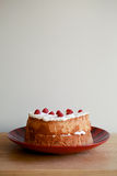Sponge Cake. A delicious sponge and cream cake on a red plate topped with a juicy raspberries royalty free stock image