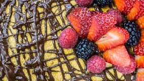 Sponge cake, chocolate on top, strawberries and raspberries, close-up stock photography