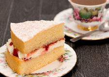Sponge cake and coffee with ornate antique crockery Stock Photos
