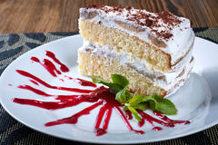 Sponge cake with cream and raspberry sauce, delicious sweet dess Stock Images