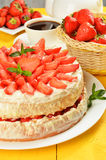 Sponge cake with cream and strawberries on yellow wooden background Stock Photography