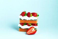 Sponge cake. Creative concept photo of a strawberry cake made of sponges on blue background royalty free stock image
