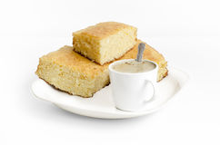 Sponge cake and a cup of coffe on white background Stock Photography