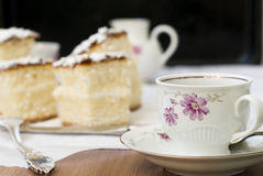 Sponge cake with a cup of coffee. Still Life with slices of sponge cake sprinkled with powdered sugar and a cup of coffee on a dark background Stock Photos