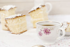 Sponge cake with a cup of coffee. Still Life with slices of sponge cake sprinkled with powdered sugar and a cup of coffee on light background Royalty Free Stock Photography